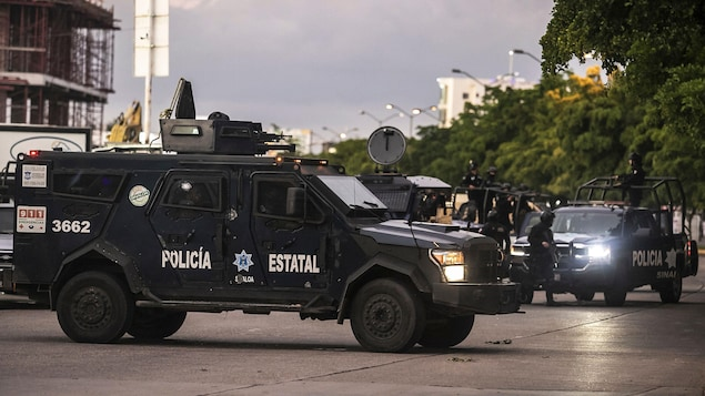 Un blindé de la police stationné en travers d'une rue.