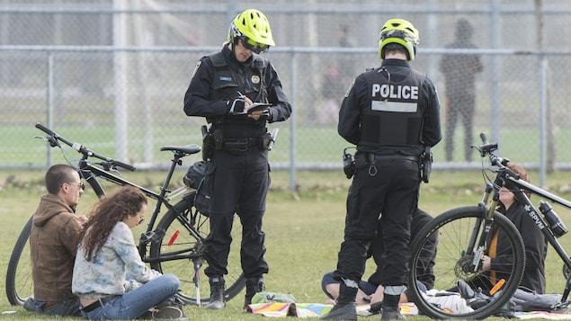 Deux policiers écrivent des contraventions alors que des gens sont assis par terre.