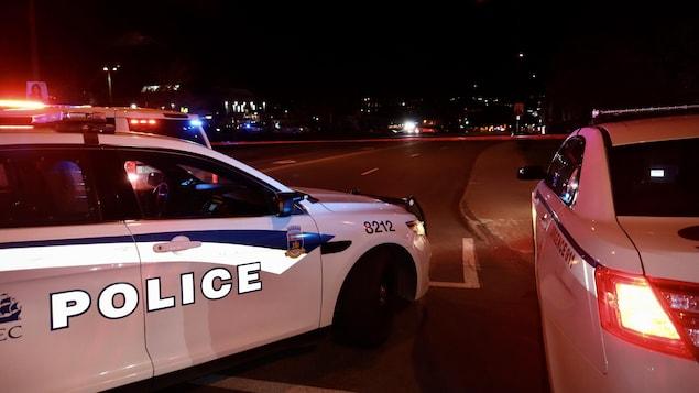 Deux voitures du Service de police de la Ville de Québec barrent une avenue de Sainte-Foy de nuit.