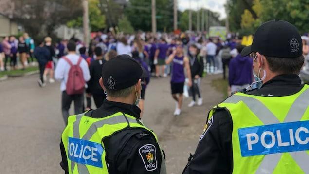 Des policiers qui surveillent des étudiants rassemblés en grand nombre dans la rue.