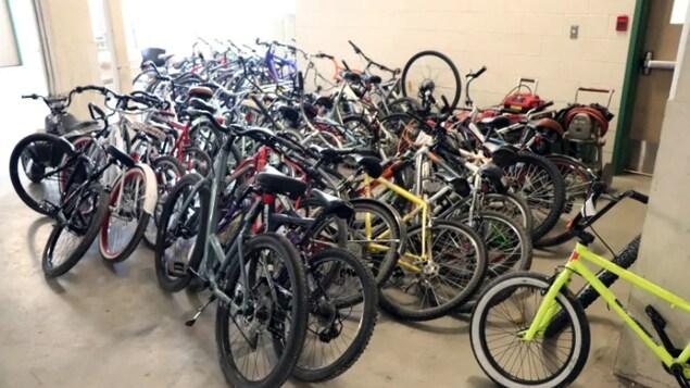 Des dizaines de vélos volés entassés dans une pièce.