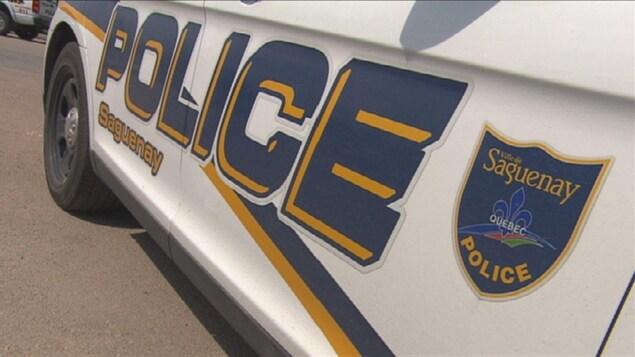 Un véhicule du Service de police de Saguenay est garé dans un stationnement.