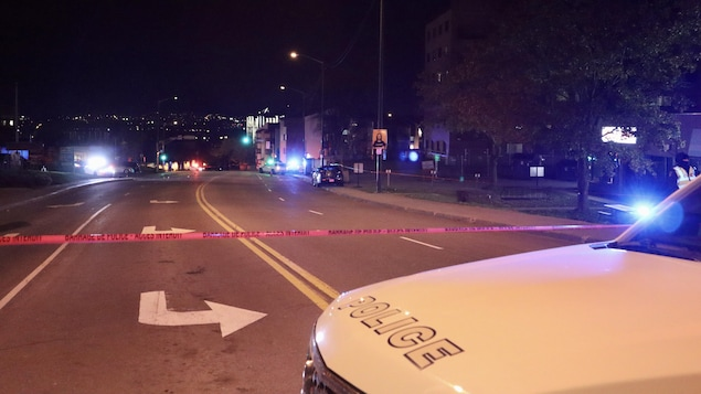 Le capot d'une voiture de police vu de près et un ruban de signalisation pour marquer un périmètre de sécurité.