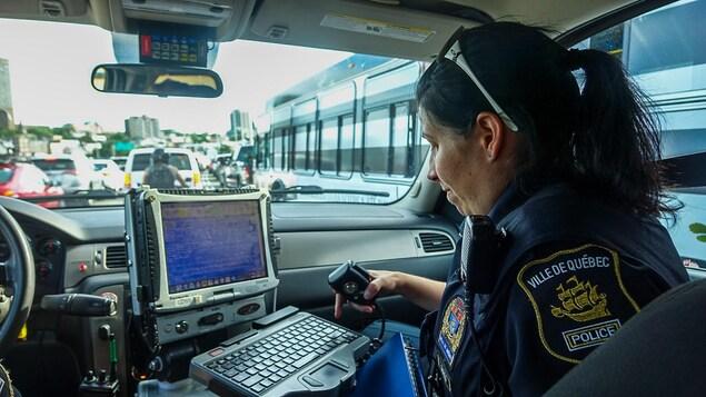 La sergente Julie Marcotte consulte l'ordinateur d'une voiture de patrouille du SPVQ.
