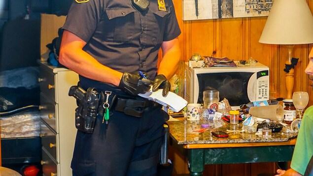 Un policier du SPVQ prend des notes lors d'une intervention dans un appartement du Vieux-Québec