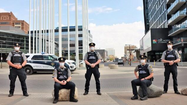 Cinq agents du Service de police de Saskatoon près d'un de leur véhicule.