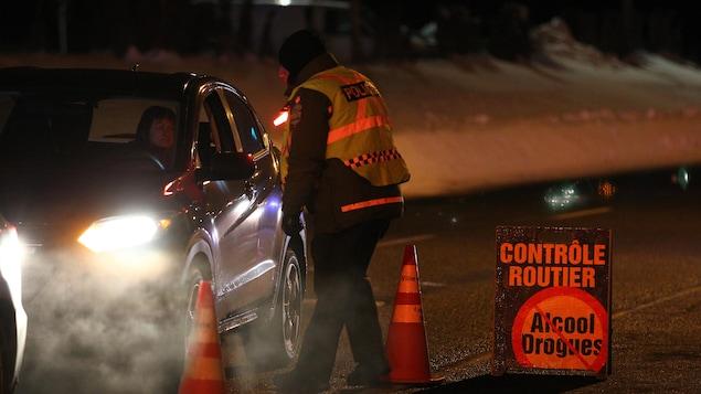 Un policier s'approche d'une voiture sur un barrage routier contre la conduite avec facultés affaiblies par une nuit d'hiver.