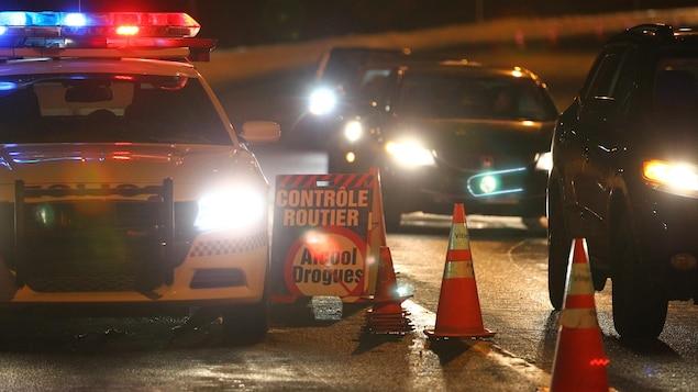 Voiture de la Sûreté du Québec au milieu d'un barrage routier visant à contrer la conduite avec facultés affaiblies.