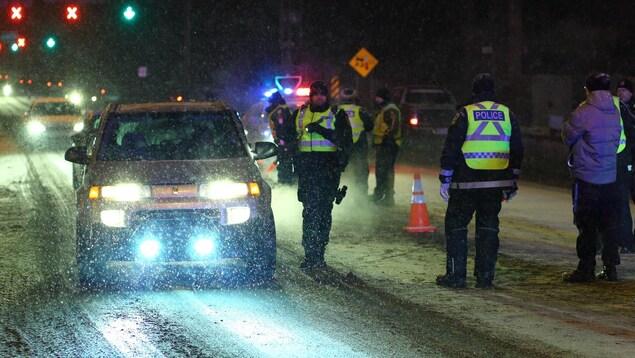 Des agents s'avancent vers des véhicules arrêtés à un barrage, en soirée.