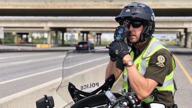 Un policier tient un radar dans ses mains.