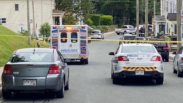 Des voitures de polices dans une rue bloquée.