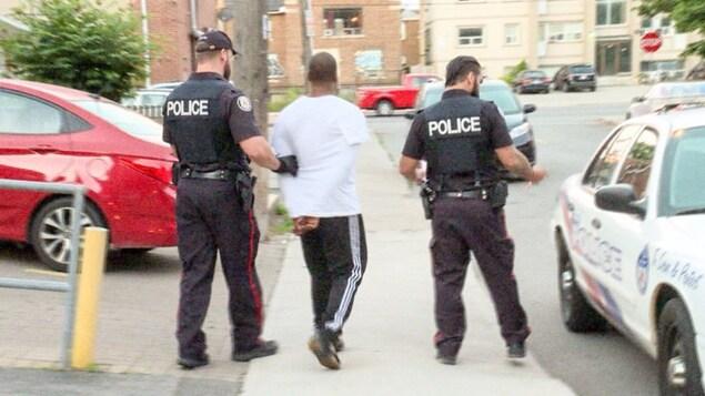 Photo d'un homme, les mains menottées derrière le dos, qui est amené par deux policiers vers une autopatrouille.