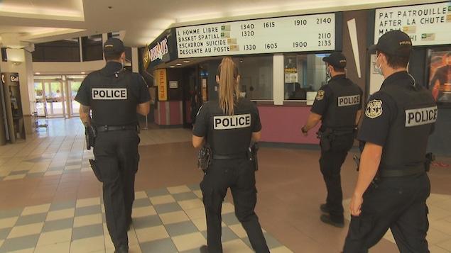 Quatre policiers marchent en direction du Cinéma Fleur de Lys.
