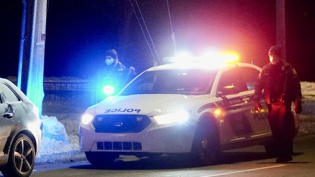 Deux policiers, avec des masques, aux côtés de leur véhicule de police.