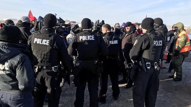 Des agents de la Police de Regina devant la raffinerie Co-op de Regina.