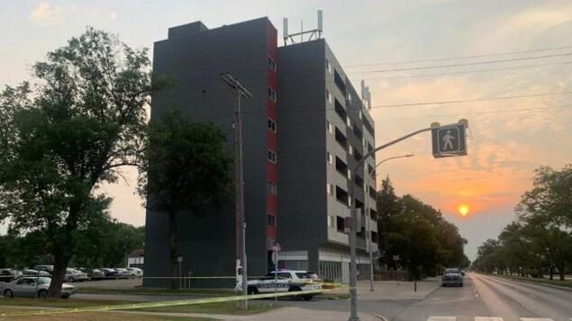 Les policiers ont délimité une scène de crime avec du ruban jaune sur le boulevard Provencher alors que le soleil se lève.