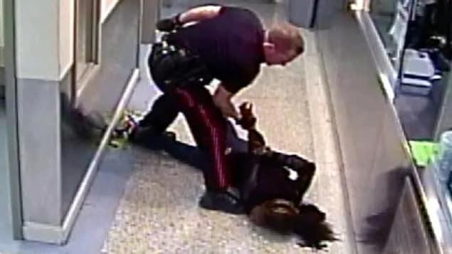 Un policier plaque au sol une femme menottée.