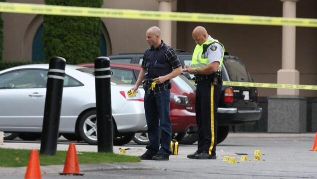 Deux policiers placent des marqueurs sur une scène de crime. Trois voitures sont garées juste derrière eux et sur le sol se trouvent des marqueurs numérotés.