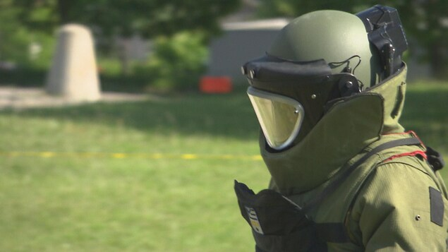Un homme vêtu d'un équipement de protection contre les engins explosifs.