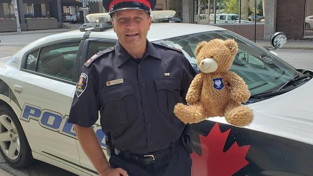 un policier tient un ourson en peluche devant une voiture de police