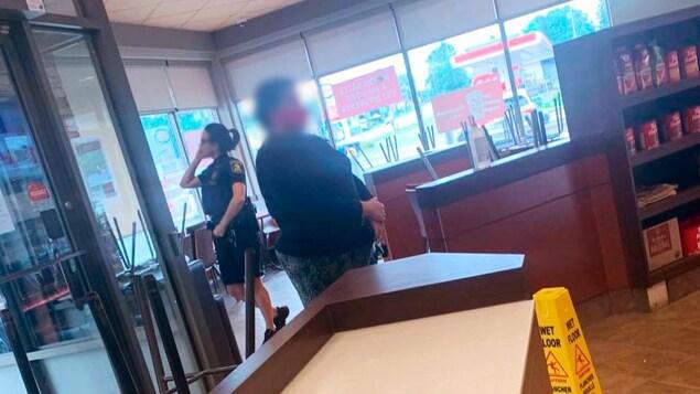 Une policière sans masque parlant au téléphone près de la porte dans un restaurant.