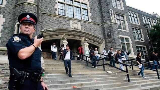 Un policier tient un talkie-walkie dans les marches à l'entrée d'une école.