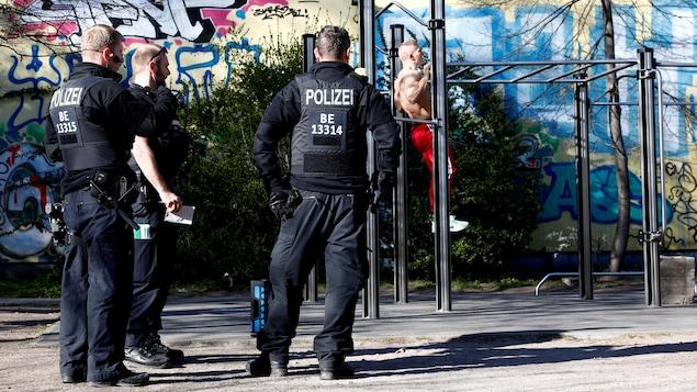 Trois policiers de dos regardent un homme faire de l'exercice.