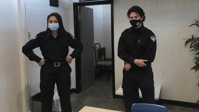 Une jeune femme et un homme autochtones habillés en policiers.