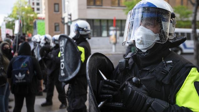 Des policiers avec leurs boucliers portant masque, casque et visière.