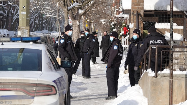 Une dizaine de policiers dans une rue enneigée d'Outremont.