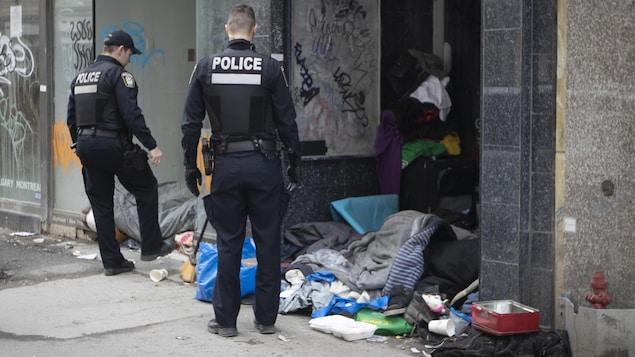 Deux policiers près d'un espace occupé par des sans-abri à Montréal.