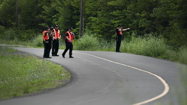 Des policiers discutent sur le bord d'une route secondaire.