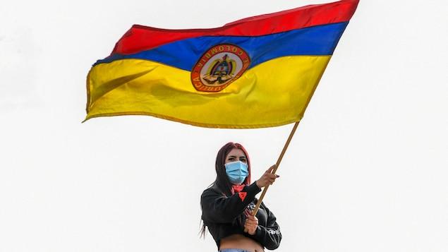 Une femme portant un masque sanitaire agite un drapeau de la Colombie lors d'une manifestation à Bogota, le 6 mai 2021.