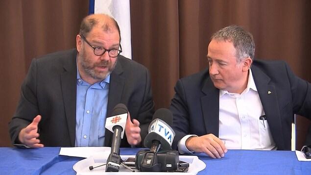 Mario Beaulieu et Yves Perron sont assis à une table, derrière des micros.