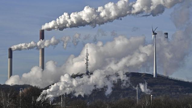 Une centrale alimentée au charbon et une raffinerie dégagent des volutes de fumée aux côtés d'une éolienne.