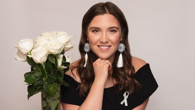 Brielle Thorsen, lauréate de l'Ordre de la rose blanche remis par Polytechnique Montréal pose à côté d'un bouquet de roses blanches