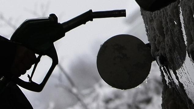 Silhouette d'une pompe à essence devant un poste d'essence couvert de verglas.
