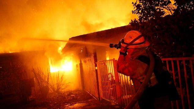 Un pompier arrose une maison.