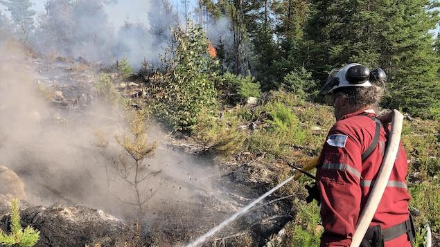 Un pompier forestier arrose un feu de forêt.