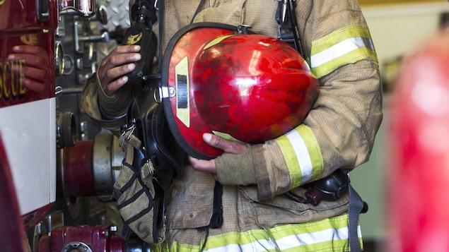 Un pompier couvert de suie tient un casque.