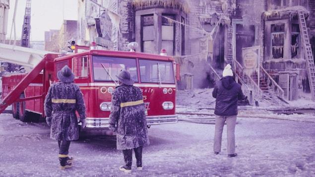 Pompiers montréalais près d'un camion suite à l'extinction d'un feu. Scène hivernale avec beaucoup de glace.