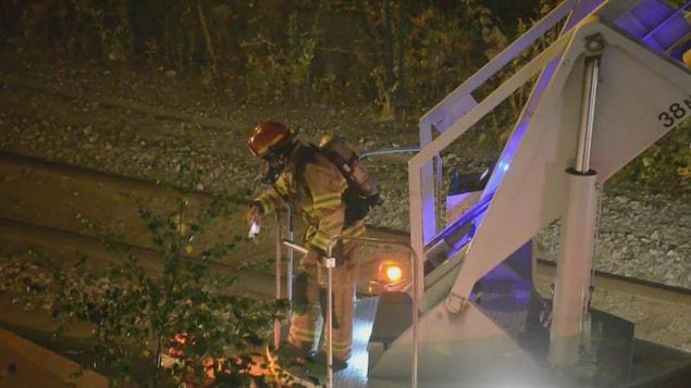 Un pompier est sur une échelle d'un camion de pompiers garé au bord d'un chemin de fer à New Westminster