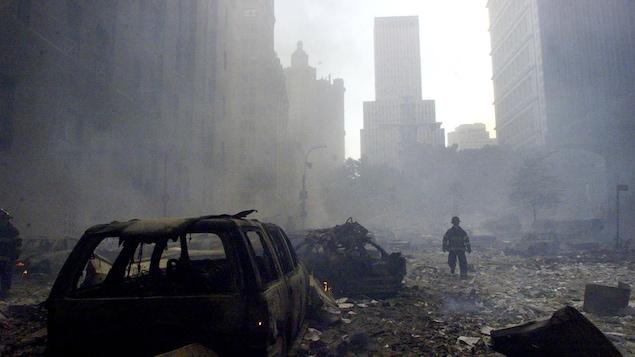 On voit la silhouette d'un pompier et les édifices de Manhattan se découpant sur un ciel enfumé. Au premier plan, des carcasses de véhicules incendiés. Le sol est jonché de débris.