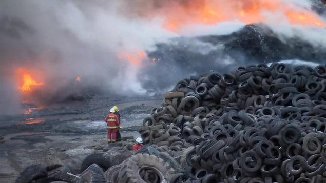 Deux pompiers près d'une pile de pneus hors d'usage regardent les flammes.