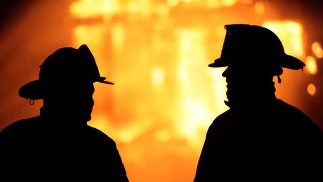 Silhouette de deux pompiers dans une lumière jaune orangée qui évoque un incendie.