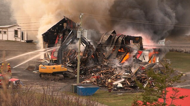 Des pompiers arrosent un tas de ruines d'où des flammes jaillissent.