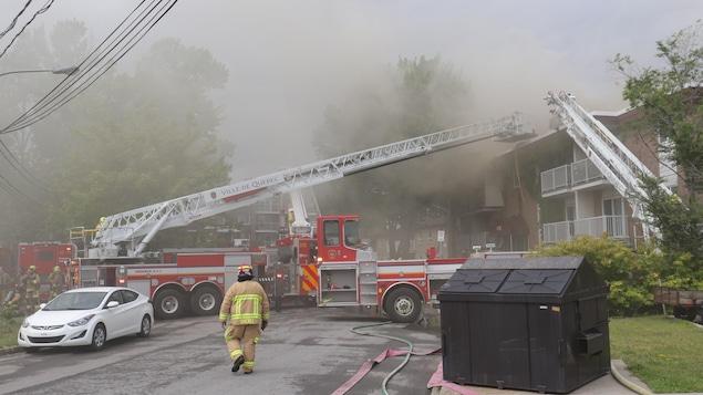 La fumée se dégage de l'immeuble pendant que des pompiers sont à l'oeuvre.