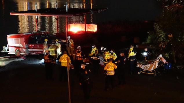 Des pompiers et des policiers s'affairent près du fleuve.