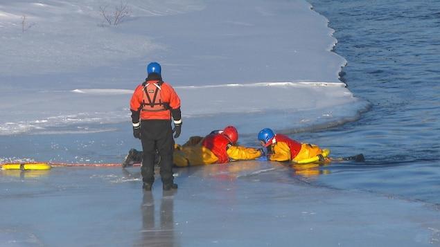 Deux pompiers couchés sur la glace tirent un troisième pompier qui fait la victime.