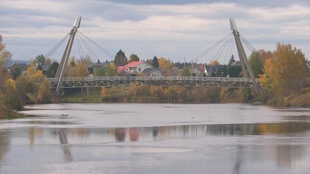 La passerelle en aluminium enjambant la rivière aux Sables.